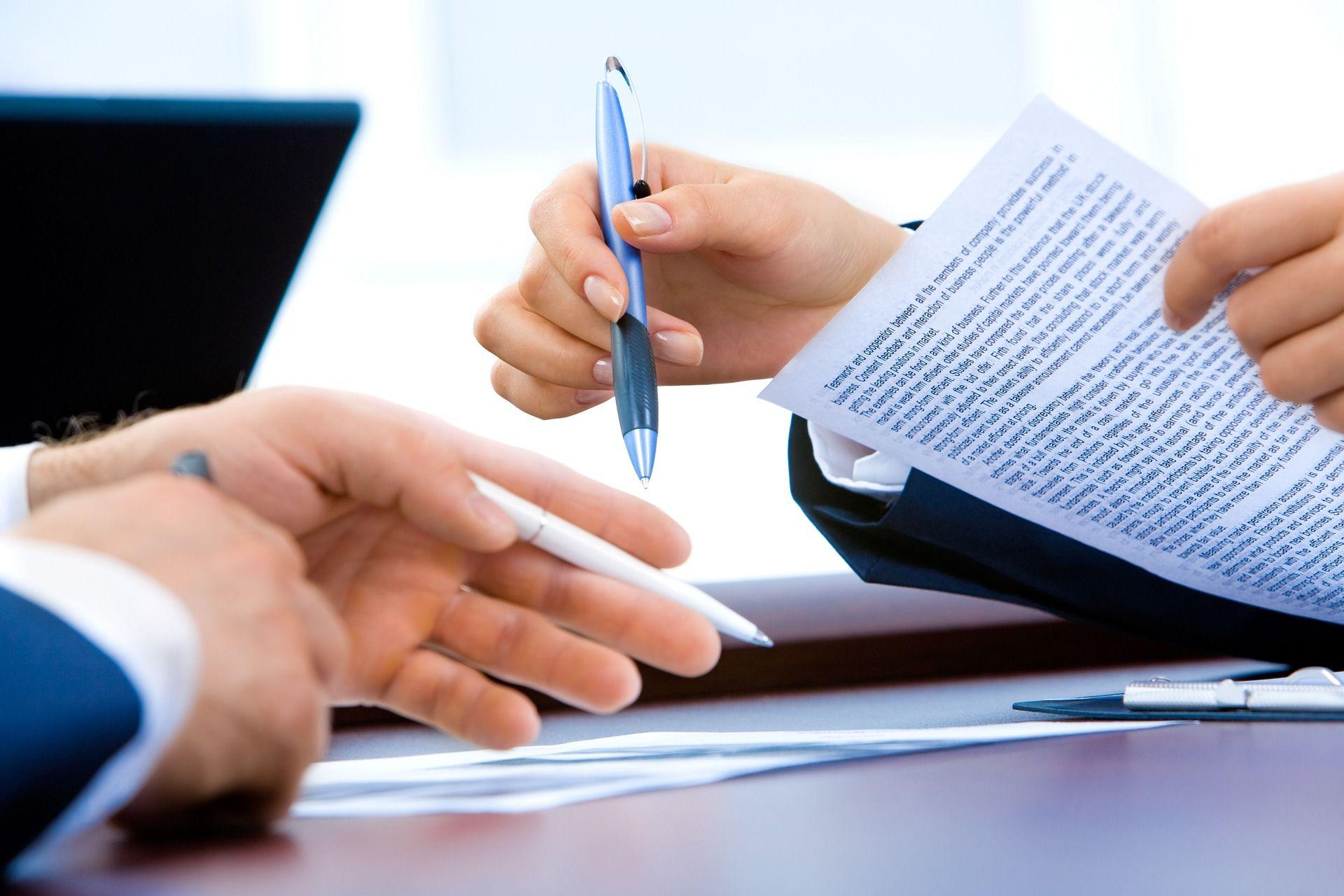 Image représentant des mains tenant des stylos et feuilles